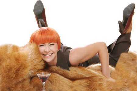 Prety red haired woman laying on fur coat with cocktail on foreground