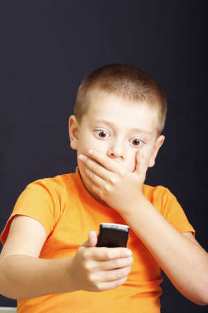 Kid in orange closing mouth by hand looking to cellular phone photo