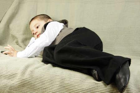 lazybones: Little idler boy laying on green sofa
