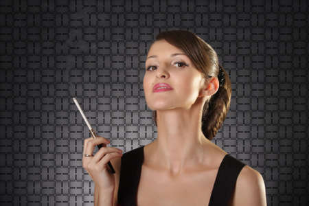 Attractive haughty lady with cigarette over dark background