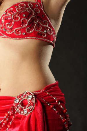 Part of belly dancer body over dark background