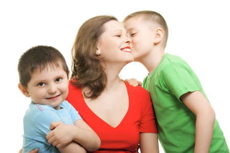 Boy kisses on mommys cheeck while other looks to camera Stock Photo