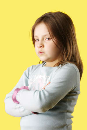 sulk: Sulk little girl with arms folded photo over yellow Stock Photo