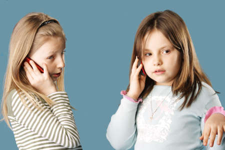 simultaneously: Two sisters talking by mobile phones simultaneously