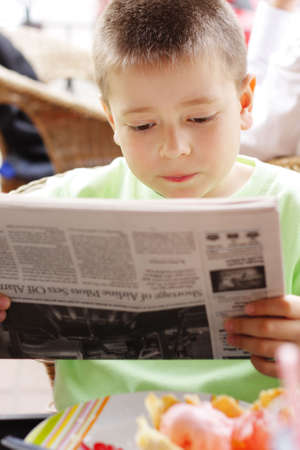 Boy in green reading newspaper at the table in outdoor cafe Stock Photo