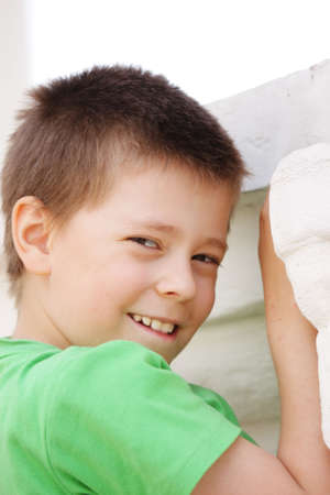 looking over shoulder: Photo of boy in green shirt looking over shoulder