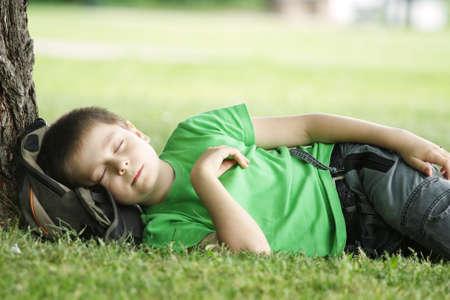 Boy in green shirt sleeping in park under tree