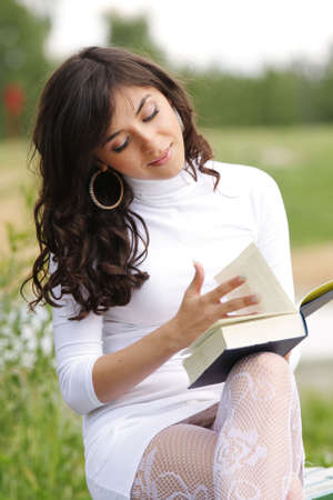 Girl in white sitting with open book in park photo