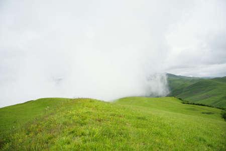 bringing: Big cloud covering green mountains bringing fog Stock Photo