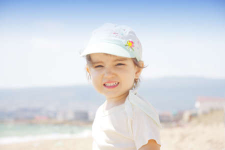Little girl on sunny beach squinting