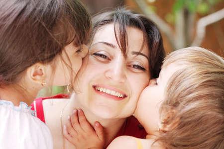 Girls kissing smiling mothers cheecks closeup photo