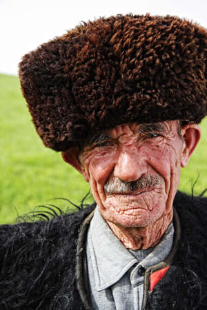 Portrait of old herder wearing traditional felt cloak and sheepskin cap Stock Photo - 5204415