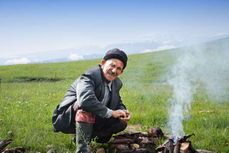 Elderly man sitting at campfire in mountains Stock Photo - 5217434