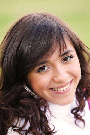sincere: Pretty girl in white smiles sincere outdoor portrait Stock Photo
