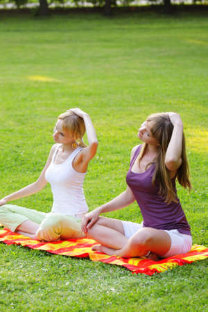 exersice: Two young women making yoga exercises in park