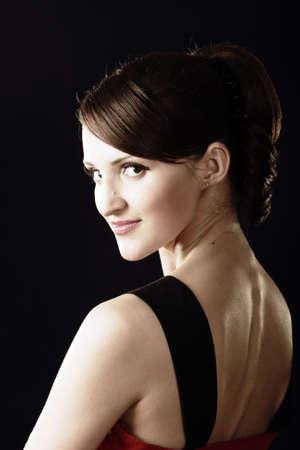 gaze: Jonge vrouw blik over schouder foto boven donker Stockfoto