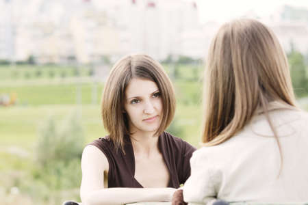 Attentive listener participating in two women conversation outdoors