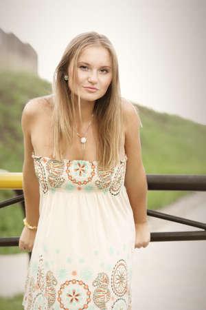 sundress: Pretty girl in sundress standing at metallic barrier outdoors