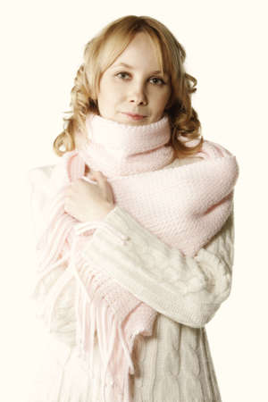 muffle: Pretty young blonde woman wraping herself up in pink scarf Stock Photo