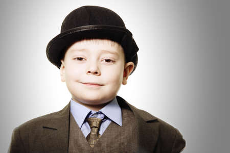 Funny smiling boy in bowler hat closeup photo