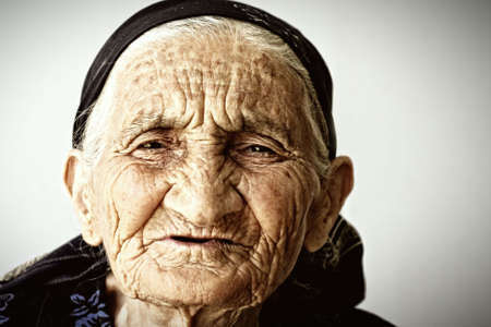 Very old woman face covere with wrinkles closeup photo Stock Photo