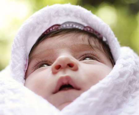coverlet: Baby wrapped in coverlet looking up outdoor photo