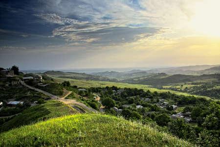 Summer sun shining over Caucasus mountain countryside photo
