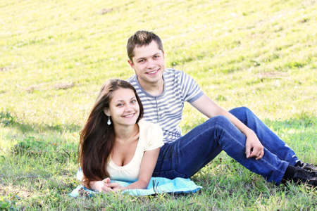 Smiling young couple settled in summer meadow photo
