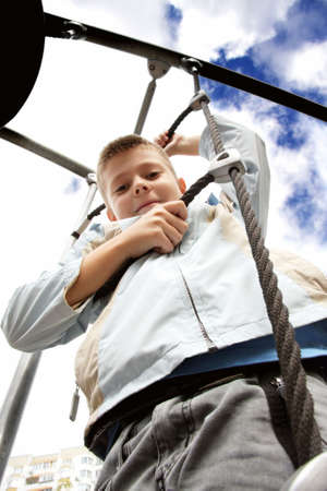 Boy in blue jacket on rope ladder against clouds on sky photo