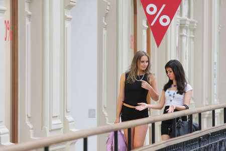 Two pretty girls at shopping chatting while walking photo