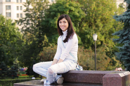 Smiling brunette girl sitting on stone bench outdoor photo Stock Photo - 5479648