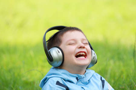 Laughing boy with headphones sitting in green meadow photo
