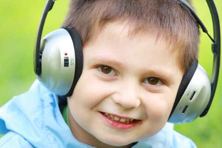 Closeup portrait of smiling little boy in headphones photo