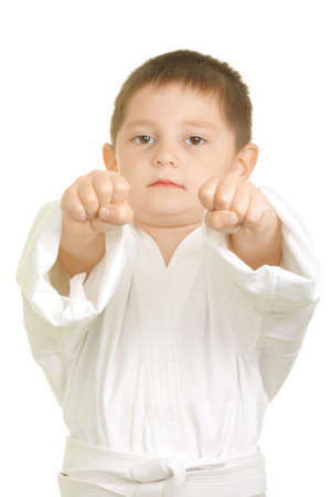 simultaneously: Little karate boy punchs with two fists simultaneously