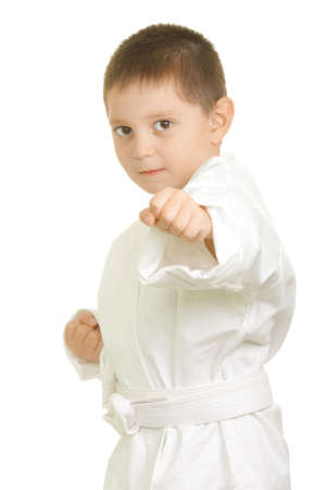 Little karate boy punches with left fist photo over white Stock Photo