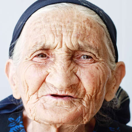 Very old hoary woman face closeup portrait against light background