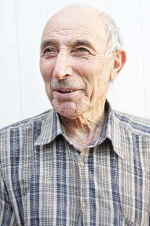 Elderly man looking aside against light background Stock Photo