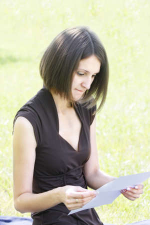Pretty young woman in brown dress reading letter outdoors photo