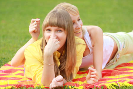 coverlet: Two pretty funny blonde friends laying on coverlet in meadow
