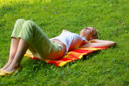 coverlet: Young blonde woman sleeping on coverlet in meadow