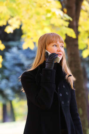 Young blond woman walks in autumn park and talks on phone photo