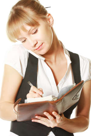 simultaneously: Pretty young businesswoman writing and listening phone simultaneously Stock Photo