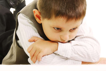 dreary: Little upset boy laying against white background