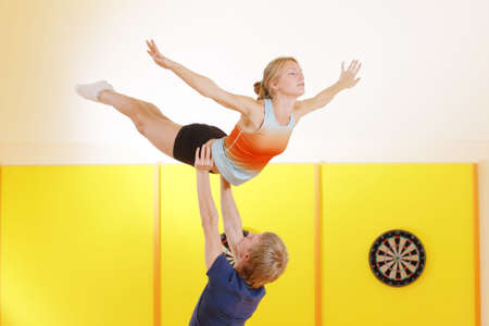 feat: Young couple training acrobatic feat in gym