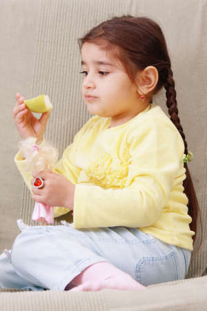 Little girl in yellow holding slice of green apple photo