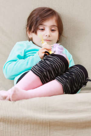Little serene girl playing with toy doll while sitting on sofa photo