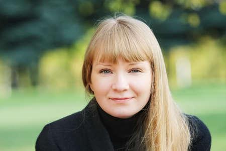 overcoat: Young serene woman in black overcoat in autumn park