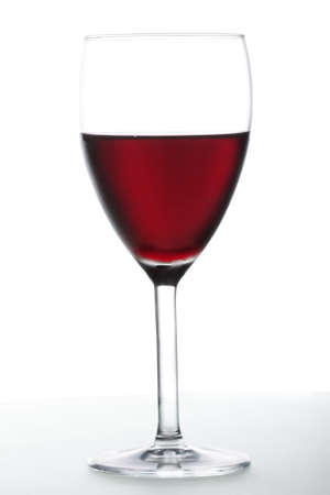 Glass of red wine against white background closeup photo