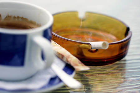 Smoking cigarette in ashtray and blue cup of coffee selective focus photo