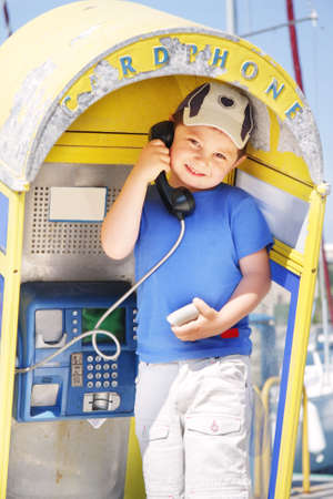 Little smiling boy in blue shirt at old rusty pay-phone